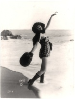 SUMMARY: Alice Maison in bathing suit, standing with one foot in ocean, muff on right hand and left hand raised. CALL NUMBER: SSF - Bathing Beauties--1918